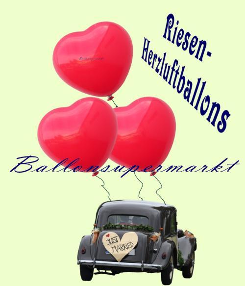 Rote Riesen-Herzluftballons schweben am Hochzeitsauto. Die Fahrt in das Hochzeitsglück mit riesigen Herzluftballons, den Luftballons der Liebe.
